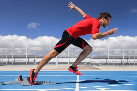 Runner athlete starting running at start of run track on blue running tracks at outdoor athletics and fiel stadium. Sprinter. Sport and fitness man running sprinting.