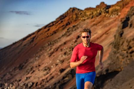 Trail runner on mountain run. Athlete man focused running training endurance. Fitness motivation.