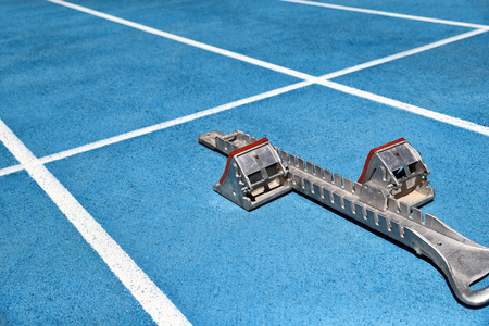 Starting blocks on blue running tracks lanes at track and field stadium. Sport accessory. Фото со стока