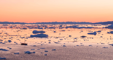 Ice and Icebergs from glacier - amazing arctic nature landscape aerial image of icefjord filled with icebergs from melting glacier Sermeq Kujalleq, Ilulissat, Greenland. Fishing boat and Midnight sun.
