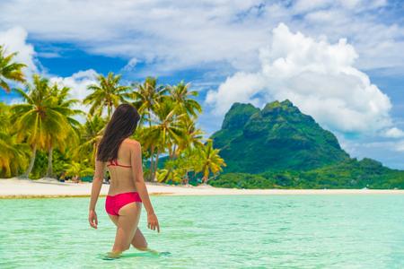 Reizen paradijs strand vrouw wandelen in het water op het strand op luxe vakantie vakantie Tahiti, Bora Bora. Mooie vrouw in rode bikini meisje op strandvakantie in Tahiti, Frans Polynesië.