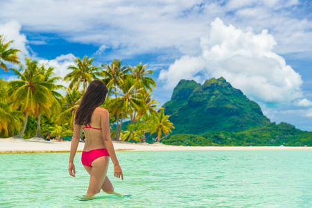 Travel paradise beach woman walking in water on beach on luxury holidays vacation Tahiti, Bora Bora. Beautiful woman in red bikini girl on beach vacation in Tahiti, French Polynesia.
