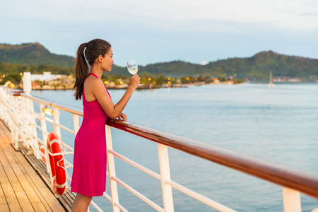 Luxury cruise ship honeymoon vacation woman drinking wine during dinner at outdoor restaurant deck of sailing boat in Tahiti, French Polynesia. Elegant lady drinking wine on balcony watching sunset.