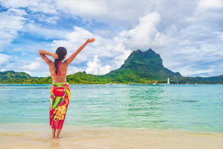 Vacances Voyage femme marchant sur la plage paradisiaque de Tahiti motu Bora Bora en vacances à Bora Bora avec le mont Otemanu. Fille heureuse portant un paréo traditionnel et un bikini à Tahiti, Polynésie française. Banque d'images