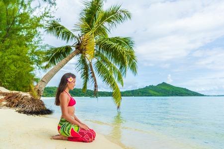 Tahiti Bora Bora Polynésie française Vacances à la plage Vacances Voyage. Femme détente assise sur la plage paradisiaque sur la plage de Matira, Bora Bora. Fille heureuse portant un paréo traditionnel et un bikini à Tahiti Banque d'images