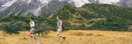 Hikers hiking on trail in mountain landscape background. Couple healthy people living an active lifestyle on Hooker Valley Track, New Zealand. Famous attraction for summer travel, banner crop.
