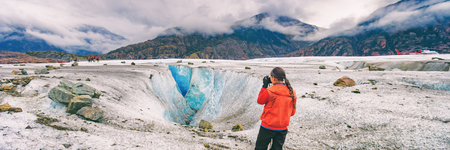 Alaska cruise travel tourist taking photo on activity excursion glacier hike in nature. Banner panorama of woman photographer on summer vacation in USA. Stock Photo