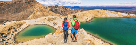 New Zealand volcanic mountain landscape in Tongariro Alpine Crossing National Park. Young people couple hikers tramping in NZ travel adventure, panoramic banner background. Stock Photo
