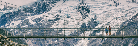 Hooker Valley Track hiking trail, New Zealand. Panoramic crop of bridge across the Hooker Valley track, Aoraki, Mt Cook National Park with snow capped mountains landscape. Banner crop. Stock Photo - 116943402