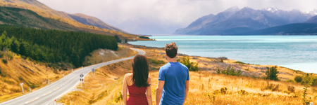 New Zealand travel people looking at Mount Cook Aoraki far in the landscape. Couple tourists walking at Peters lookout, banner panorama copy space on background. Stock Photo