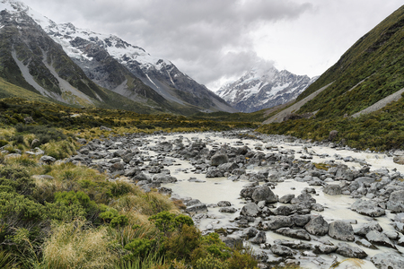 Hooker Valley Track hiking trail, New Zealand. River leading to Hooker lake with glacier over view of Aoraki Mount Cook National Park with snow capped mountains landscape. Stock Photo - 115457798