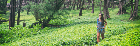 Nature hike travel hiking girl walking in lush forest landscape panorama. Happy Asian hiker woman on trail path in green grass. Panoramic banner.