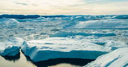 Climate Change and Global Warming - Icebergs from melting glacier in icefjord in Ilulissat, Greenland. Aerial image of arctic nature ice landscape.
