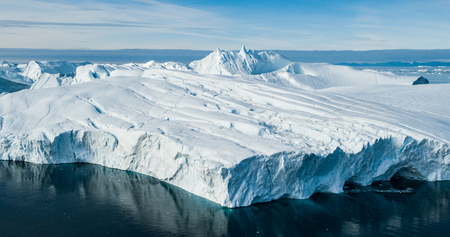 Global Warming and Climate Change - Giant Iceberg from melting glacier in Ilulissat, Greenland. Aerial drone of arctic nature landscape famous for being heavily affected by global warming. Stock Photo