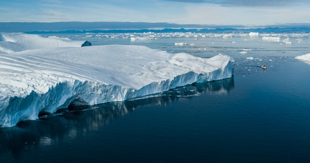 Climate Change and Global Warming - Giant Iceberg from melting glacier in Ilulissat, Greenland. Aerial drone of arctic nature landscape famous for being heavily affected by global warming. Boat. Stock Photo