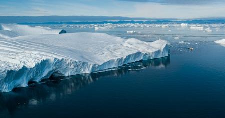 Zmiana klimatu i globalne ocieplenie - Olbrzymia góra lodowa z topniejącego lodowca w Ilulissat na Grenlandii. Powietrzny dron arktycznego krajobrazu słynącego z silnego wpływu globalnego ocieplenia. Łódź. Zdjęcie Seryjne