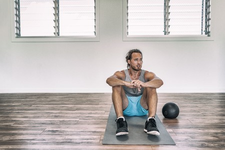 Gym workout man training floor exercises with weighted slam ball or medicine ball taking a break tired sweating thinking of disappointment. Stock Photo