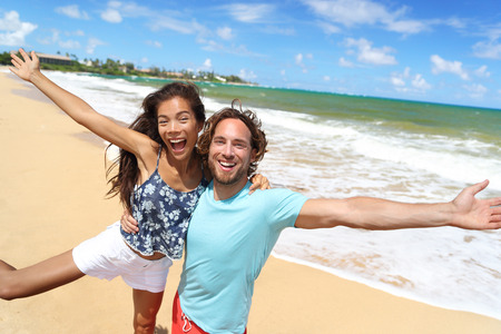 Happy people jumping screaming of fun on beach summer vacation travel in Hawaii. Laughing young Asian woman with Caucasian man, tourists couple friends on holiday.