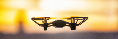 Drone flying outside in sky sunset banner panorama. Closeup of drone quadcopter with security camera outdoor.