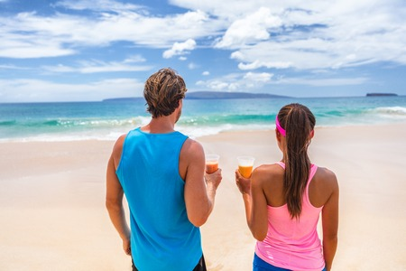 Healthy people active lifestyle. Fitness runners couple on beach drinking breakfast fruit juice in smoothie cups looking at ocean. Summer background. Stock Photo