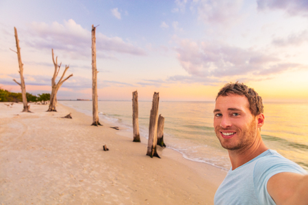 Selfie man tourist on travel holiday on Florida beach vacation. Lovers key state park at sunset, smiling young adult alone on summer trip.
