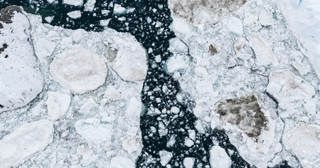 Icebergs drone aerial image top view - Climate Change and Global Warming. Icebergs from melting glacier in icefjord in Ilulissat, Greenland.