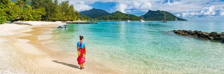 Femme touristique de voyage à la plage de la Polynésie française sur l'île de Huahine excursion en croisière sur les vacances de Tahiti. Fille portant un sarong polynésien jupe bannière culture panoramique. Banque d'images