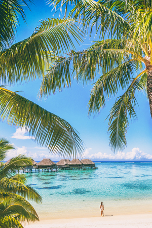 Tahiti luxuy travel resort overwater bungalow hotel in Bora Bora idyllic holiday woman in paradise vertical background with copy space on palm trees.