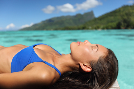 Bikini woman relaxing sunbathing on luxury resort on overwater deck. Sexy Asian model lying down sun tanning on turquoise ocean Tahiti water.
