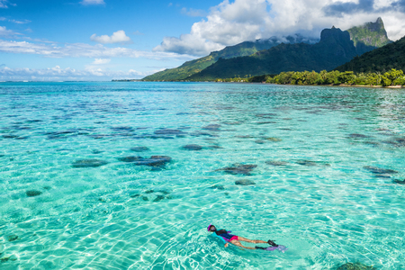 Luxury travel vacation tourist woman snorkeling in Tahiti ocean, Moorea island, French Polynesia. Snorkel swim girl swimming in crystalline waters and coral reefs. Stock Photo