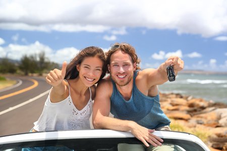 Road trip travel couple showing car keys on summer vacation. Happy young people adventure lifestyle. Carsharing, rideshare, autostop cor young adults buying new car, rental insurance young people.