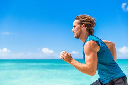 Healthy sport runner man running sprint on beach ocean background. Sports athlete active lifestyle in summer outdoor tropical landscape.