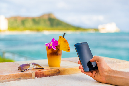 Phone app man texting taking mobile phone picture of Hawaii mai tai drink cocktail at Hawaii beach bar. Glass with flower, pineapple, sunglasses. Cellphone screen with diamond head, Honolulu vacation. Stock Photo