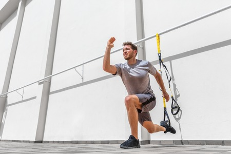 Fitness suspension straps man training legs with suspended lunge exercise at gym. Lower body workout. Banco de Imagens