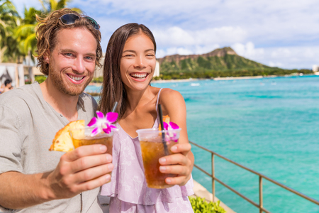 Happy hour party people toasting cheers at Waikiki beach bar, Honolulu hawaii drinking mai tai cocktails having fun. Multiracial couple on hawaiian summer travel holidays.