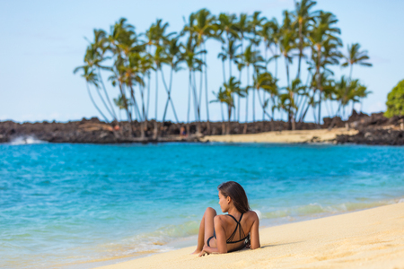 Hawaii beach summer vacation travel in Big Island, Hawaii, USA. Hawaiian secluded beach destination woman relaxing lying down on white sand at tropical holiday sun tanning. Skin care suntan concept. Stock fotó