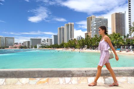 Waikiki beach Honolulu Hawaii tourist woman on summer travel vacation walking in city. Skyline background landscape.