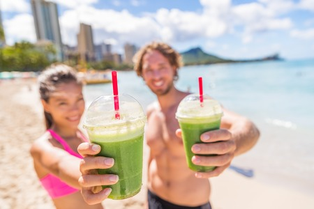 Fitness couple drinking green smoothie at beach. Man and woman holding vegetable smoothies after running sport fitness training. Healthy clean eating lifestyle concept. Stock Photo