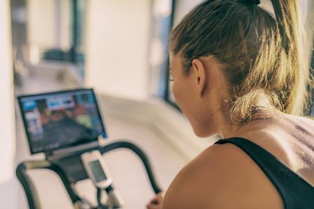 オンラインクラスの女性が自転車の運動のために屋内で静止した自転車機器でトレーニングを行うスマートフィットネスホームワークアウトバイクスクリーン。屋内サイクリング。人の背中に汗を当てる。