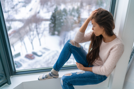 Winter depressed sad girl lonely by home window looking at cold weather upset unhappy. Bad feelings stress, anxiety, grief, emotions. Asian woman portrait. 版權商用圖片