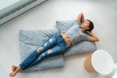 Mode de vie à la maison femme asiatique heureuse se détendre allongée sur des oreillers de sol de salon relaxant contemplative en regardant les fenêtres. Nouveau condo appartement satisfaction propriétaire jeune fille profitant de la maison.