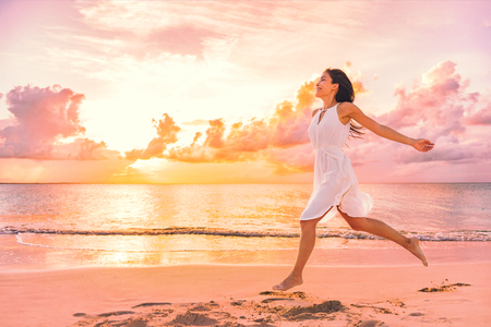 Freedom wellness well-being happiness concept. Happy carefree Asian woman feeling blissful jumping of joy on peaceful beach at sunset. Serenity, relaxation, mindfulness, stress free concepts. Reklamní fotografie