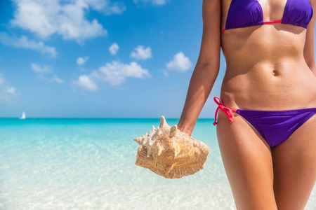 Beautiful beach bikini woman holding a conch shell on tropical summer background. Caribbean life holiday concept. UNRETOUCHED body.