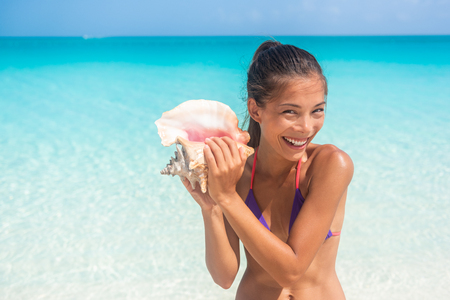 Happy tourist woman enjoying Caribbean vacation holiday on beach holding seashell conch on tropical destination. Asian girl smiling having fun.