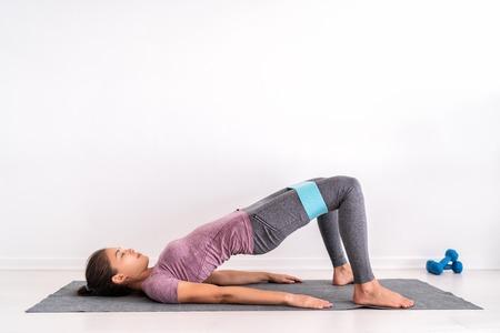 Ejercicios de banda de aro de resistencia Entrenamiento de niña en forma en el piso haciendo ejercicios de abducción de puente de glúteos para tonificar los músculos de los glúteos y activar la pérdida de peso. Foto de archivo