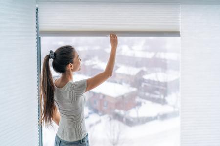 Home Jalousien Jalousien Frau, die während des Wintermorgens Jalousie öffnet. Asiatisches Mädchen, das moderne kabellose Luxusvorhänge von oben nach unten hält. Standard-Bild