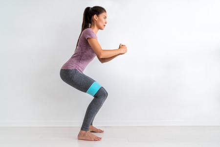 Resistance band fitness woman doing squat exercise with fabric booty band stretching strap. Crab walk squatting workout girl training at home. Stock Photo