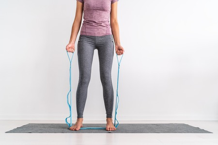 Resistance band fitness at home woman training with strap with loops for various exercises on exercise mat. Fit girl working out side bend ab muscles, bent over chest rowing pullup. Stock Photo