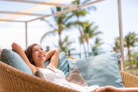 Mujer de vida de casa de hotel de lujo relajarse disfrutando de muebles de sofá de patio al aire libre. Hermosa joven asiática multirracial relajante día soñando con una rica jubilación anticipada en una casa tropical de escapada.