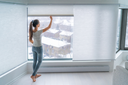 Woman closing cellular shades on apartment window keeping energy and heat indoors with honeycomb blind curtain. Cordless pleated shades in modern home living lifestyle. Interior decor design. 免版税图像 - 116701899